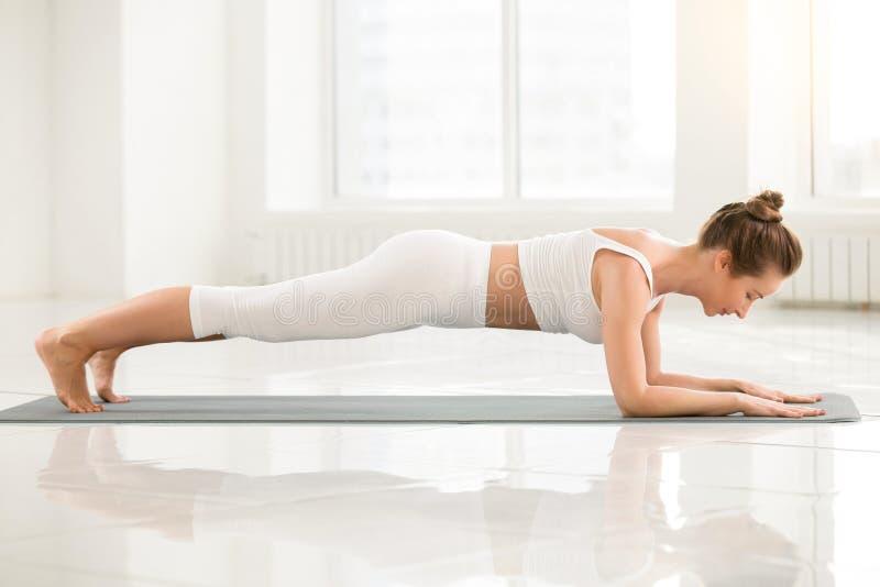 Jeune femme se tenant dans la pose de planche de dauphin, backgrou blanc de couleur photographie stock
