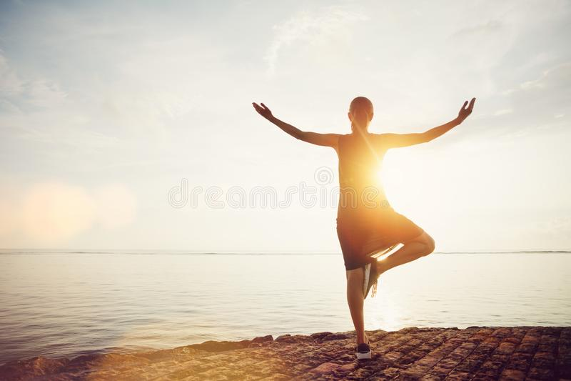 Jeune femme se tenant dans la pose de yoga sur la plage et rencontrant le lever de soleil image stock