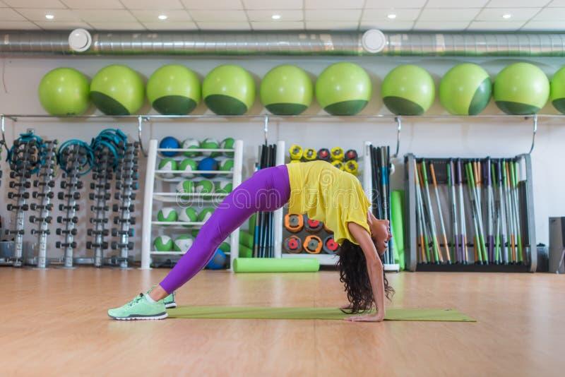 Jeune femme se tenant dans la posture de crabe sur le tapis dans le studio de forme physique tandis que le yoga de pratique s'exe photos stock