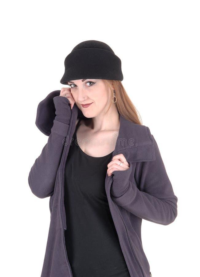 Jeune femme se tenant dans le manteau et le chapeau d'hiver image stock