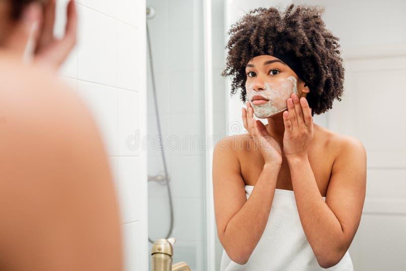 Jeune femme se tenant devant un miroir images stock