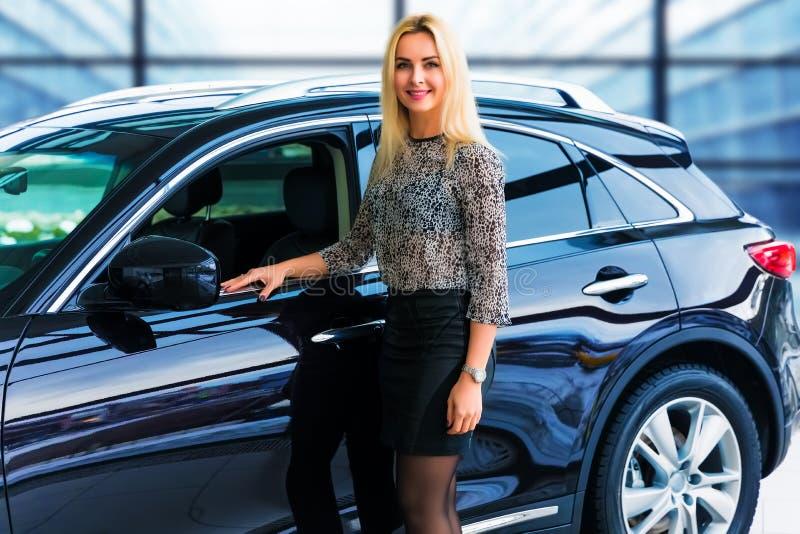 Jeune femme se tenant devant une voiture de luxe image stock