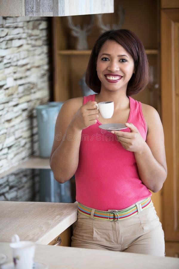 Jeune femme se tenant en café potable de cuisine photos libres de droits