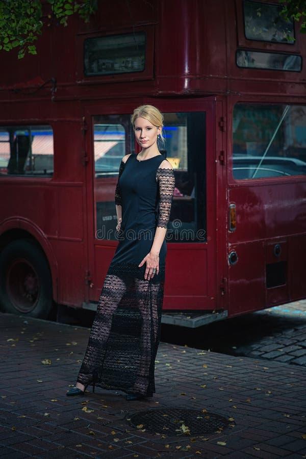 Jeune femme se tenant près de l'autobus rouge photographie stock