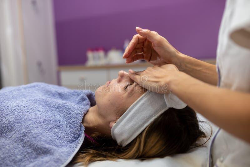 Jeune femme se trouvant sur la table de massage obtenant un traitement facial photos libres de droits