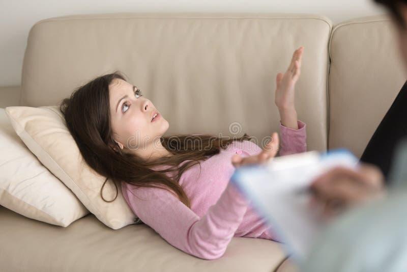 Jeune femme se trouvant sur le divan et parlant, visite au psychologue photo libre de droits