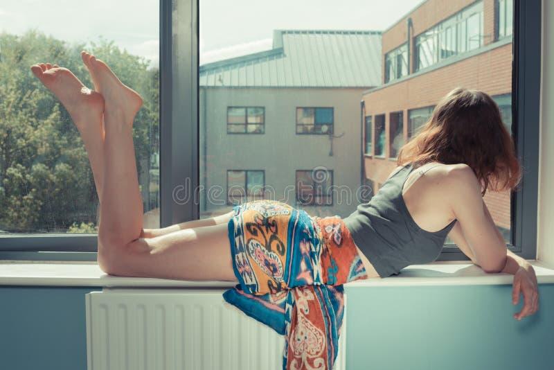 Jeune femme se trouvant sur le filon-couche de fenêtre images stock