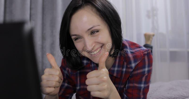 Jeune femme se trouvant sur le lit et ayant la causerie visuelle utilisant le webcam sur l'ordinateur portable photo libre de droits