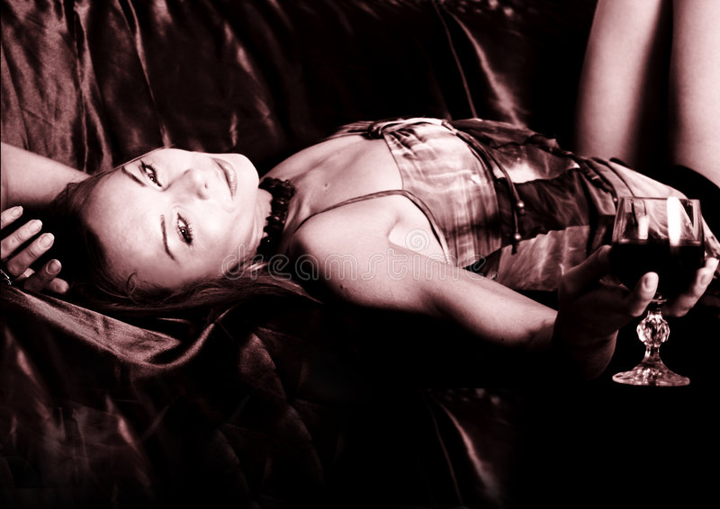 Jeune femme se trouvant sur le sofa photographie stock libre de droits