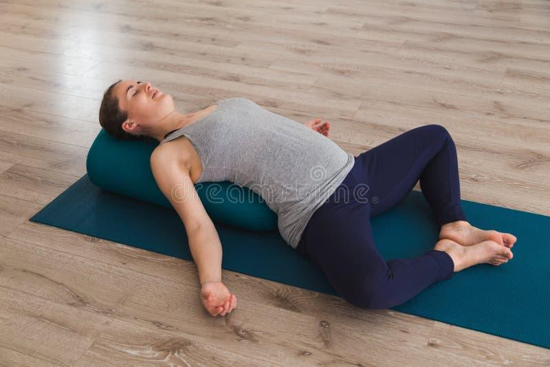 Jeune femme se trouvant sur le tapis de yoga utilisant le coussin de traversin image stock