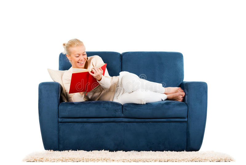 Jeune femme se trouvant sur un sofa affichant un livre image stock