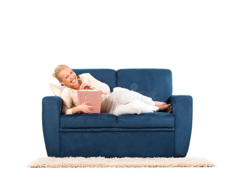 Jeune femme se trouvant sur un sofa mangeant du maïs éclaté image libre de droits