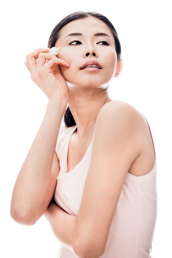 Jeune femme semblant partie tout en appliquant la crème anti-vieillissement d'oeil photos libres de droits