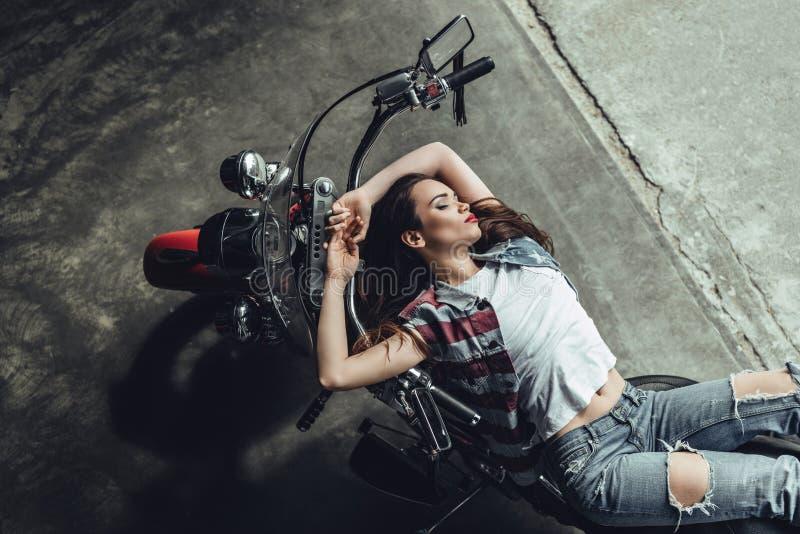 Jeune femme sensuelle de brune posant sur la moto image stock