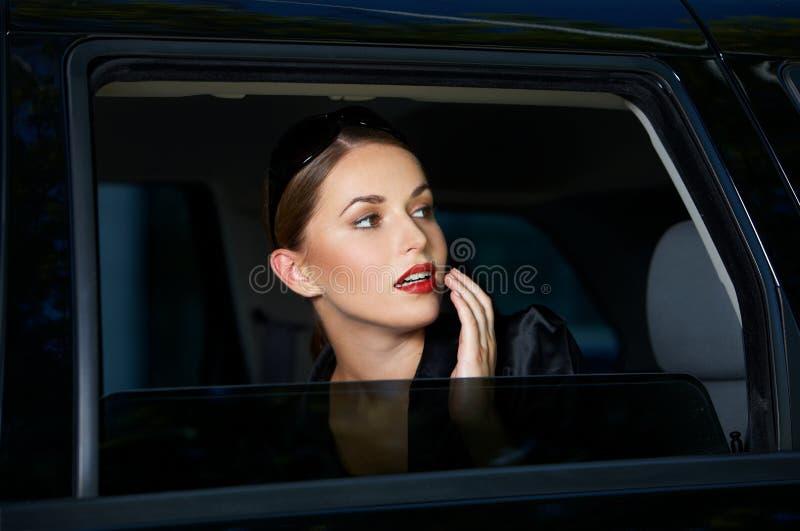 Jeune femme sensuelle regardant hors d'une fenêtre de voiture photos libres de droits