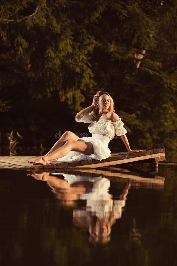 Jeune femme sensuelle s'asseyant par le lac à la pose de coucher du soleil ou de lever de soleil photo libre de droits