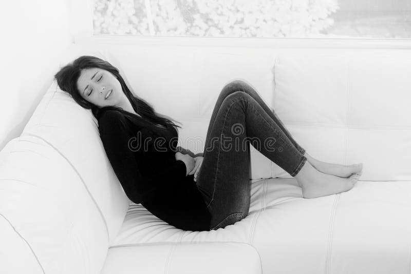 Jeune femme sentant la douleur forte de règles se reposer sur le sofa à la maison noir et blanc photographie stock