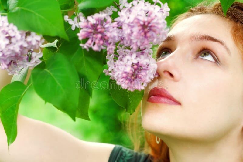Jeune femme sentant le blo lilas image stock