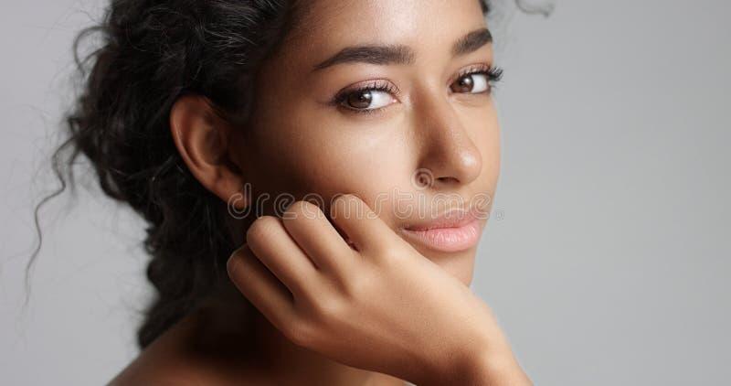 Jeune femme sereine heureuse yeux idéaux olives avec de beaux peau et de peau et de brun de cheveux bouclés dans le studio images stock