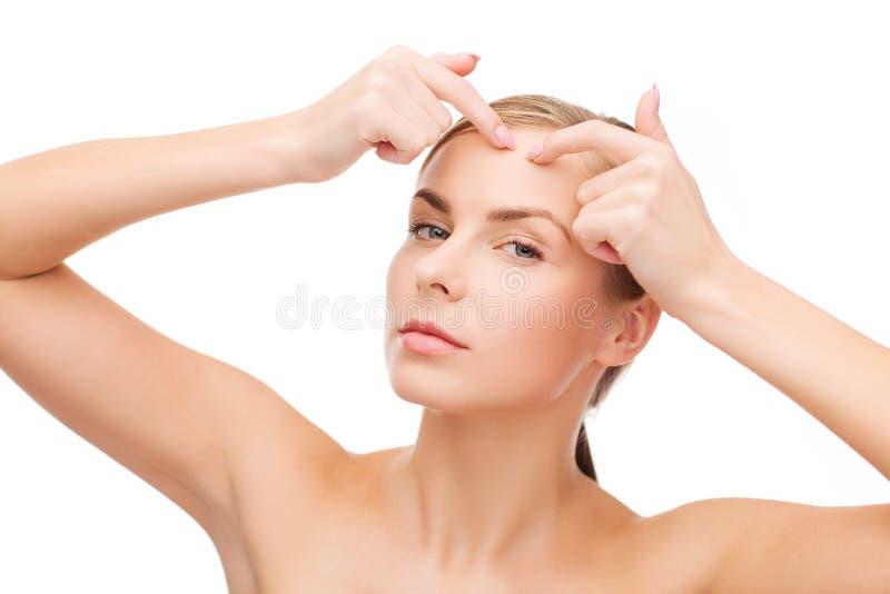 Jeune femme serrant des taches d'acné photos libres de droits