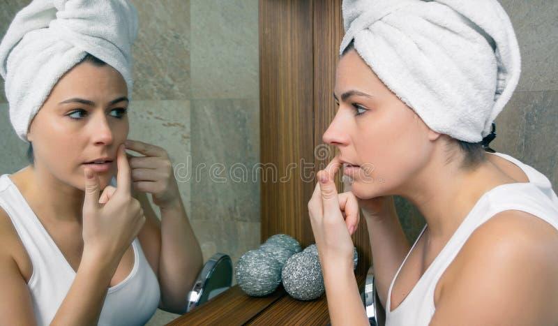 Jeune femme serrant un bouton d'acné dans le miroir photos libres de droits