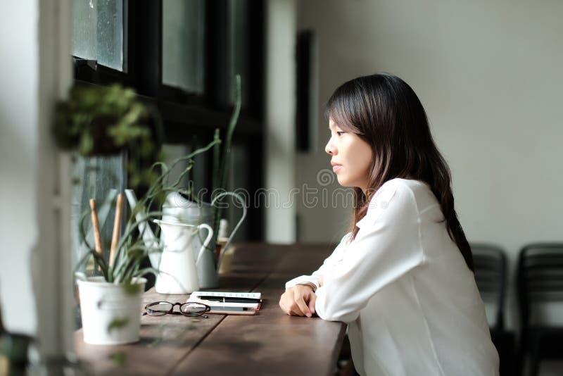 Jeune femme seul s'asseyant par la fenêtre ressemblez à son triste et W image libre de droits