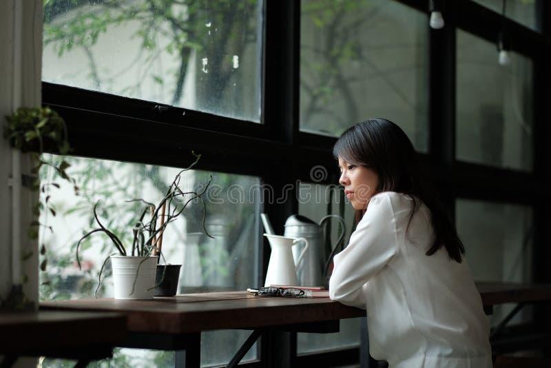 Jeune femme seul s'asseyant par la fenêtre ressemblez à son triste et W photo libre de droits