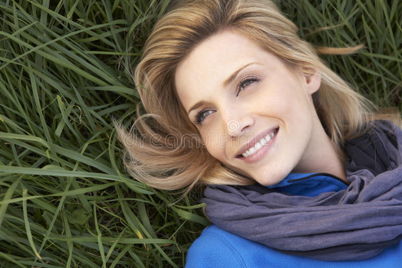 Jeune femme seul se trouvant sur l'herbe photo stock