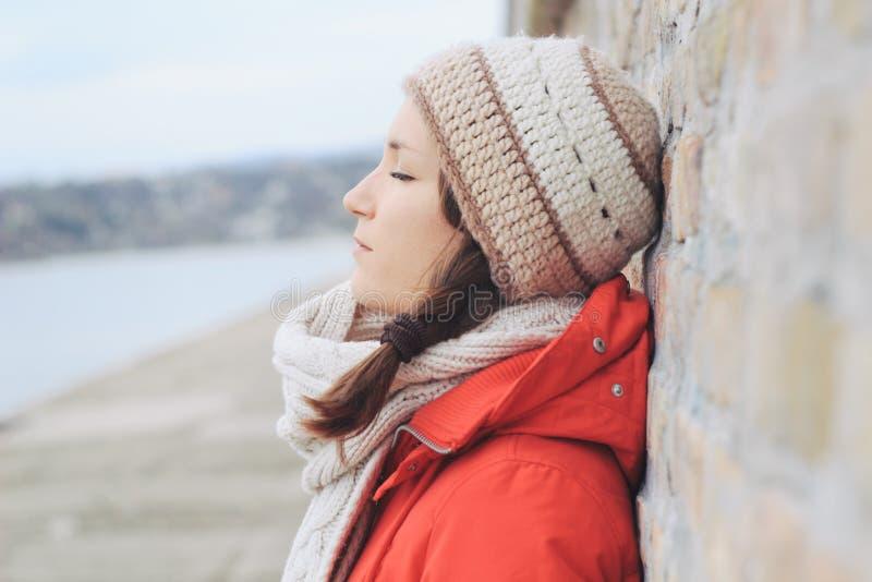 Jeune femme seule réfléchie dans des vêtements d'hiver photographie stock libre de droits