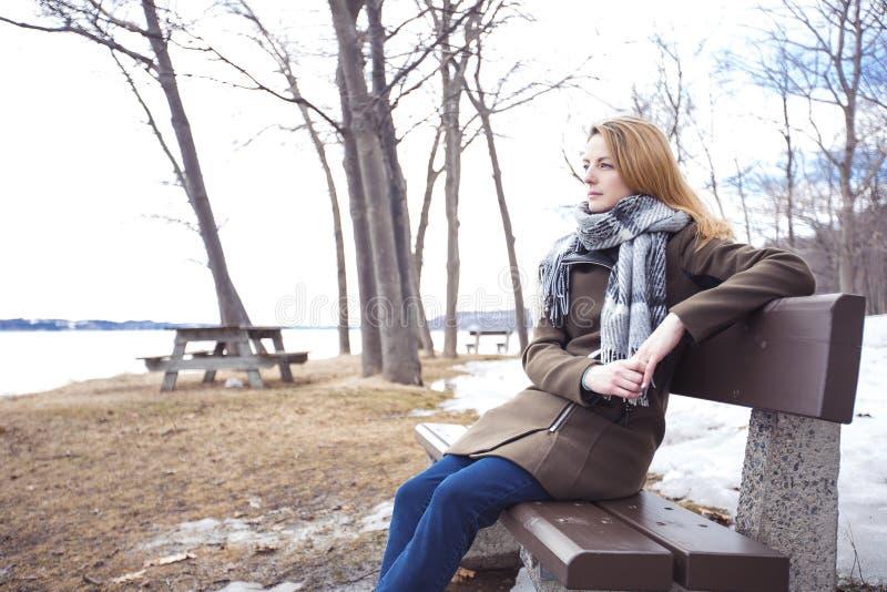 Jeune femme seule sur le banc en parc photo libre de droits