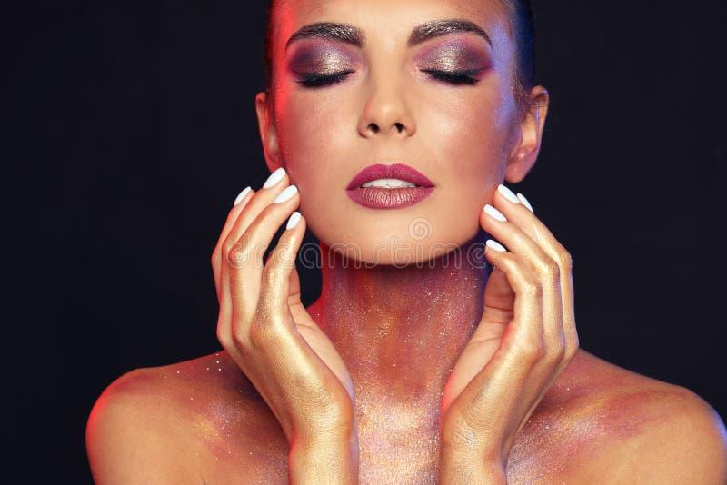 Jeune femme sexy avec le maquillage de scintillement sur le noir image libre de droits