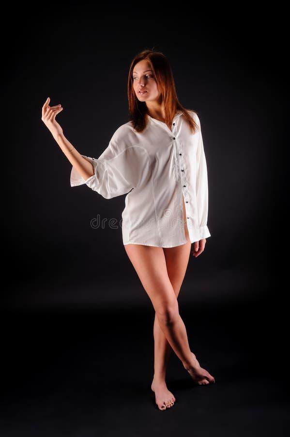 Jeune femme sexy dans la chemise et le pantalon blancs au noir photos stock