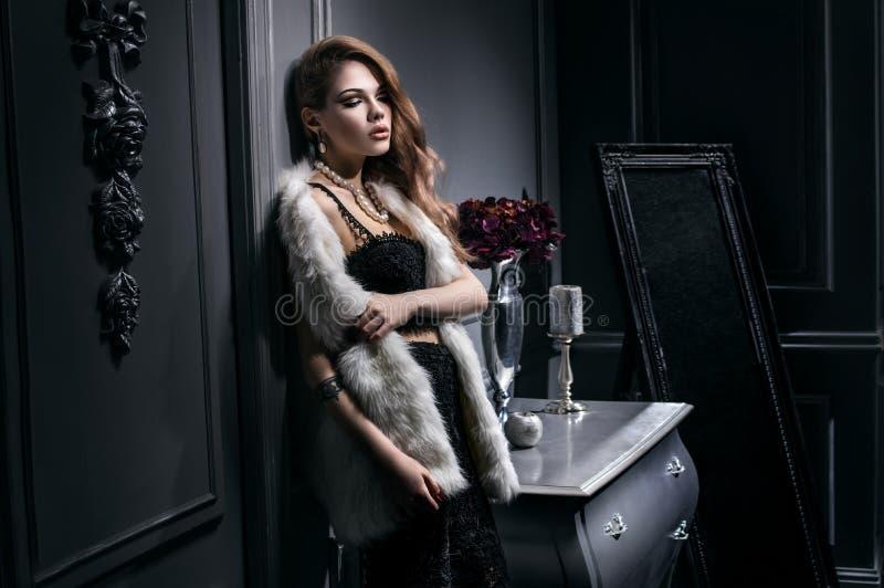 Jeune femme sexy dans la robe noire et la veste blanche de fourrure photo stock