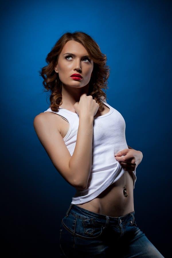 Jeune femme sexy dans le dessus de réservoir blanc de jeans image stock
