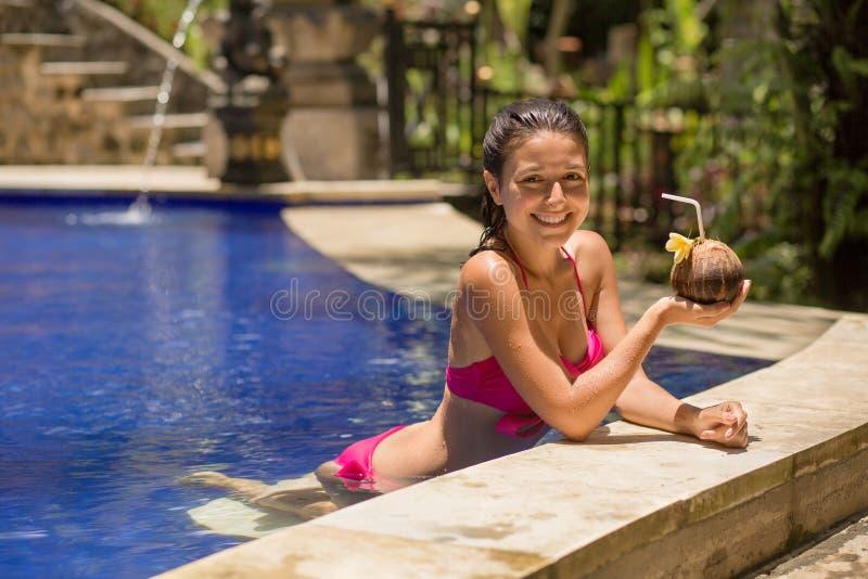 Jeune femme sexy dans le maillot de bain rose ayant la boisson de noix de coco dans la piscine des vacances photographie stock