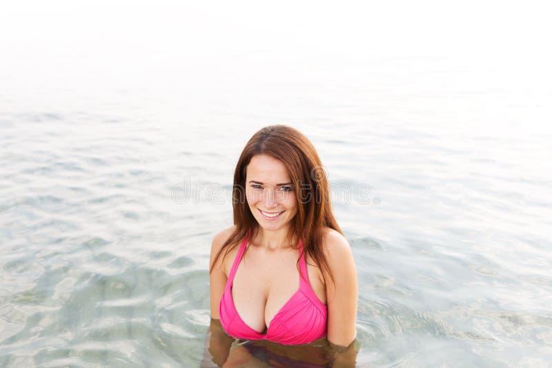 Jeune femme sexy dans un maillot de bain dans l'eau de mer photos libres de droits
