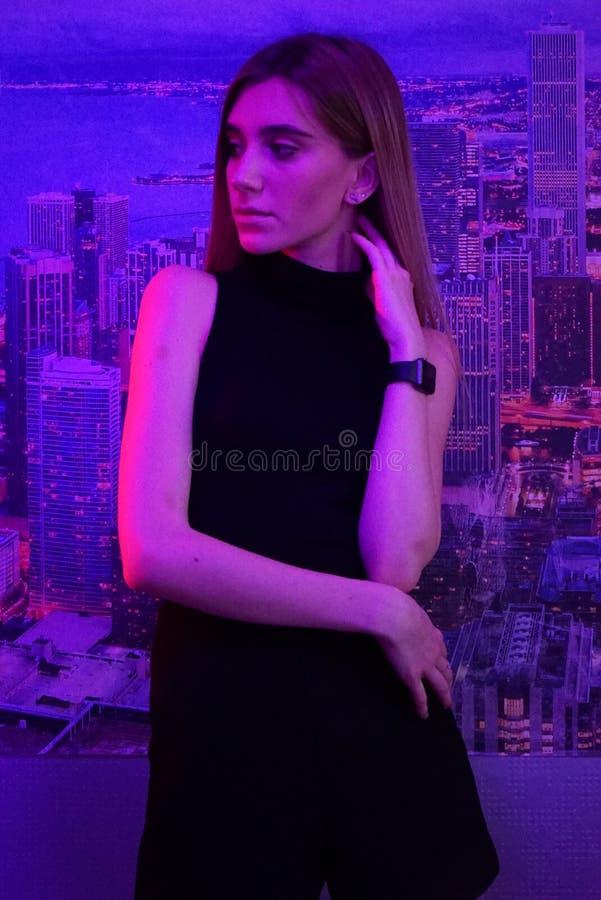 Jeune femme sexy de beauté posant au-dessus du néon de ville de nuit et du fond roses dramatiques de ville photos libres de droits