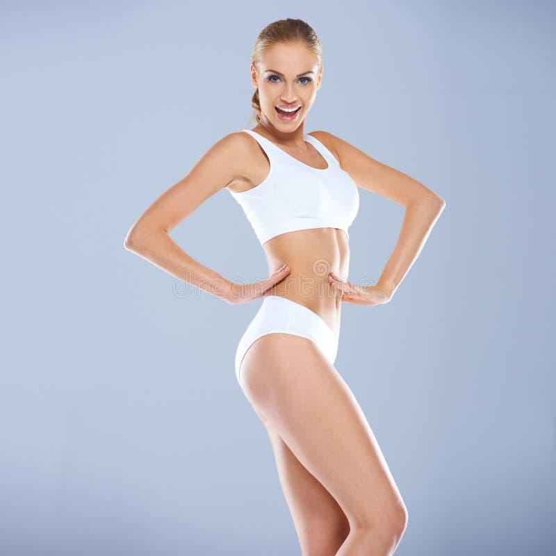 Jeune femme sexy de sourire dans l'équipement blanc de forme physique photo stock