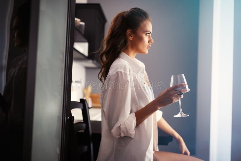 Jeune femme sexy en vin potable de lingerie ? la maison photo stock