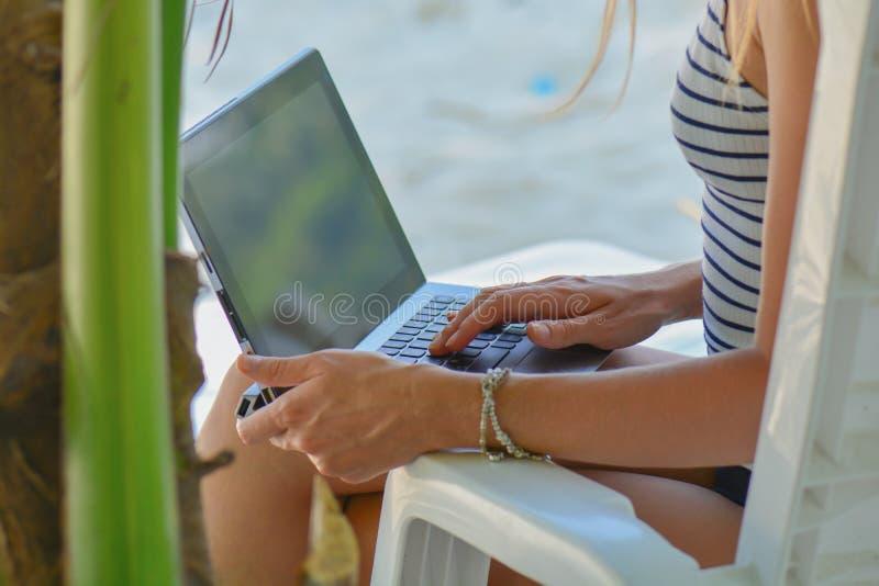 Jeune femme sexy ? l'aide de l'ordinateur portable sur la plage Fonctionnement d'ind?pendante de fille Concept tropical de vacanc photographie stock libre de droits