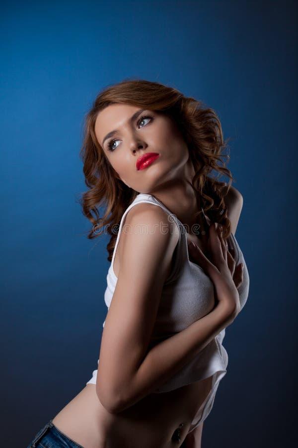 Jeune femme sexy posant en jeans et réservoir blanc photographie stock libre de droits