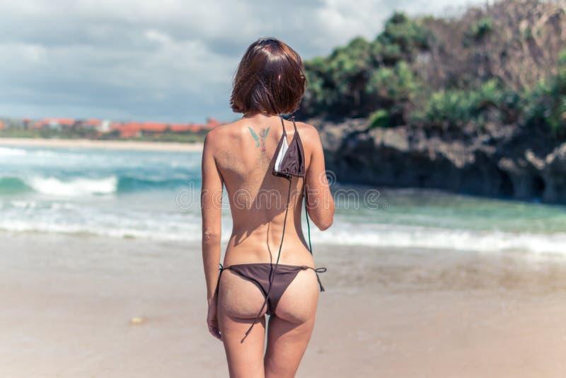Jeune femme sexy sans soutien-gorge sur la plage tropicale de l'île de Bali Concept de liberté de fille de bikini l'indonésie image libre de droits