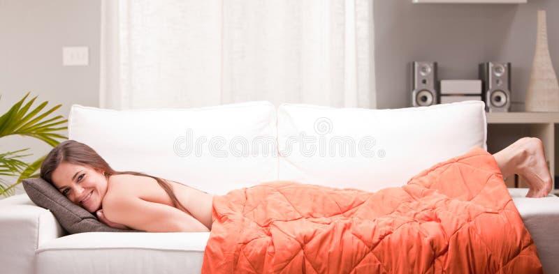 Jeune femme sexy souriant sur un divan image libre de droits