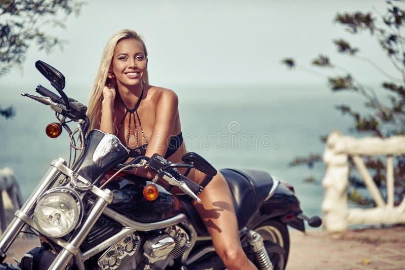 Jeune femme sexy sur le motocycle photographie stock