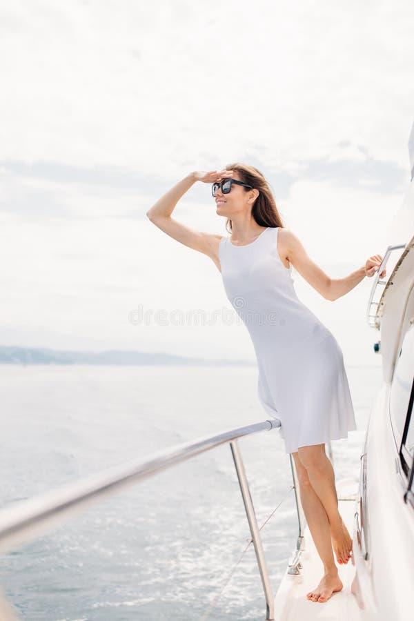 Jeune femme sexy sur son yacht privé au coucher du soleil photographie stock