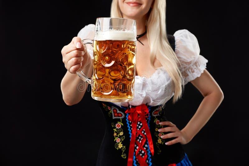 Jeune femme sexy utilisant un dirndl avec la tasse de bière sur le fond noir image libre de droits