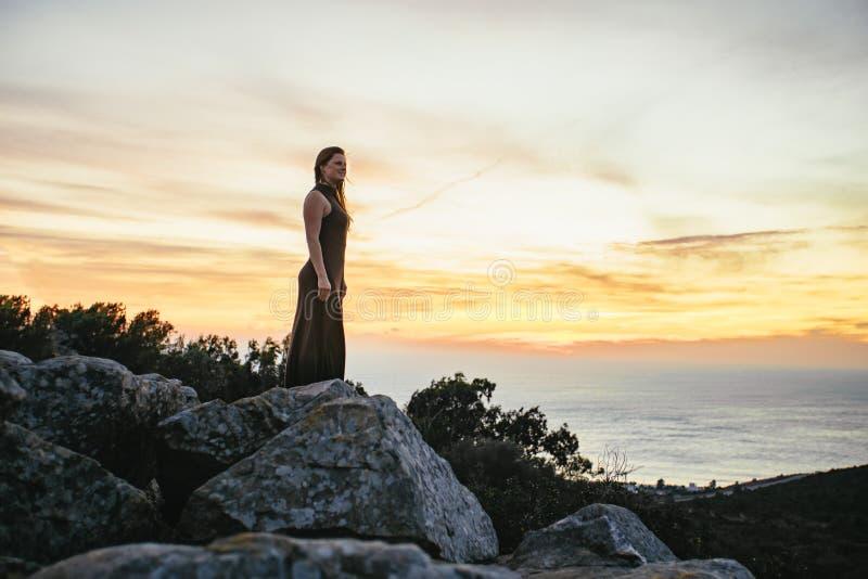 Jeune femme silhouettée contre un coucher du soleil orange images stock