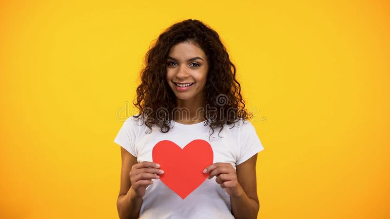 Jeune femme sincère tenant le présent en forme de coeur rouge de coupe-circuit le jour de valentines photographie stock