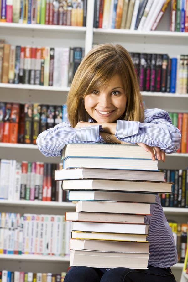 Jeune femme smilling s'asseyant dans la bibliothèque photo stock