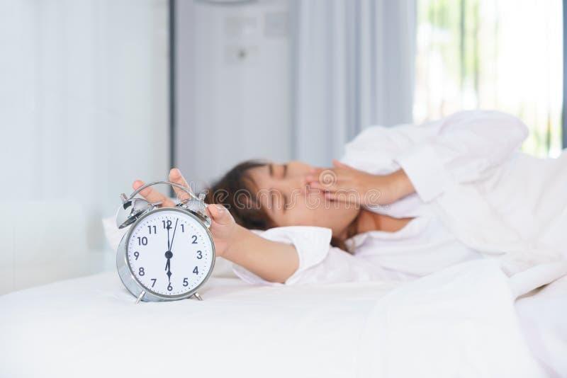 Jeune femme somnolente étirant la main au réveil de essai de mise à mort dedans images stock